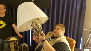 John Robert holding up a horn in a lampshade at MAGfest 2018